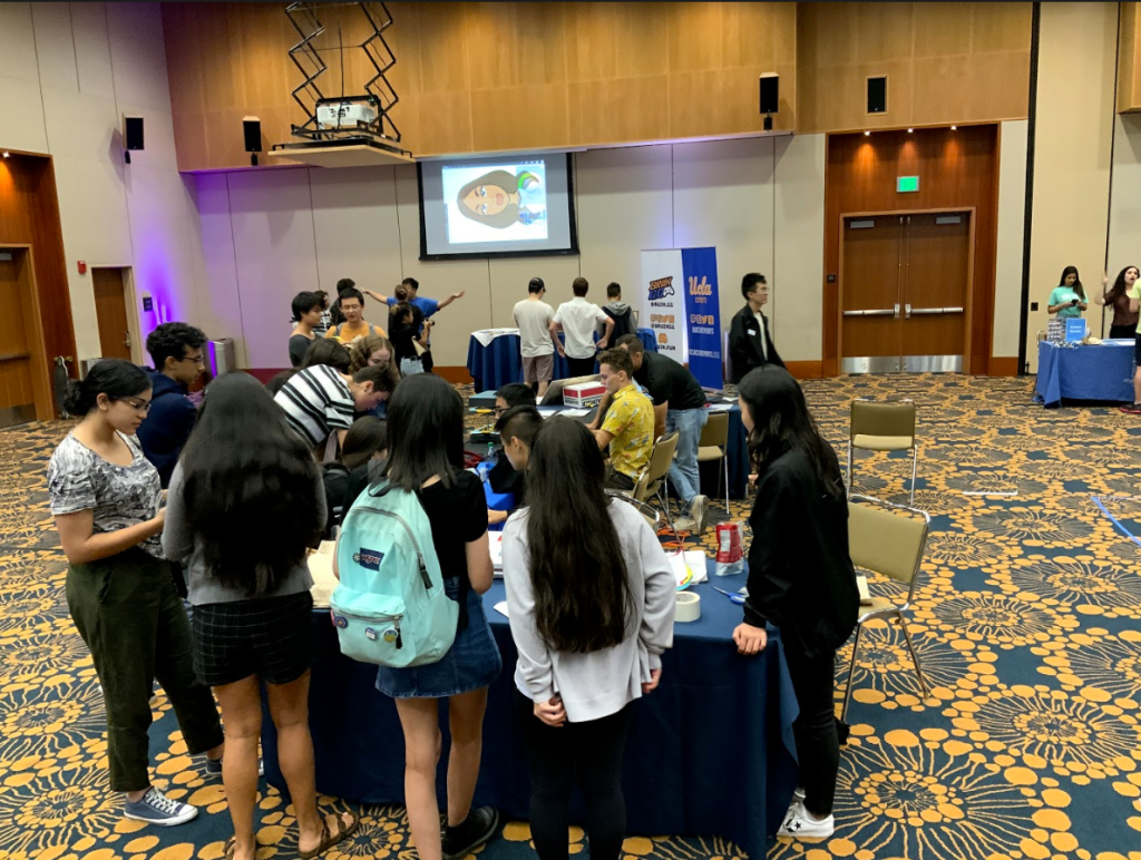 A group of students huddled around the UCLA Makerspace Booth
